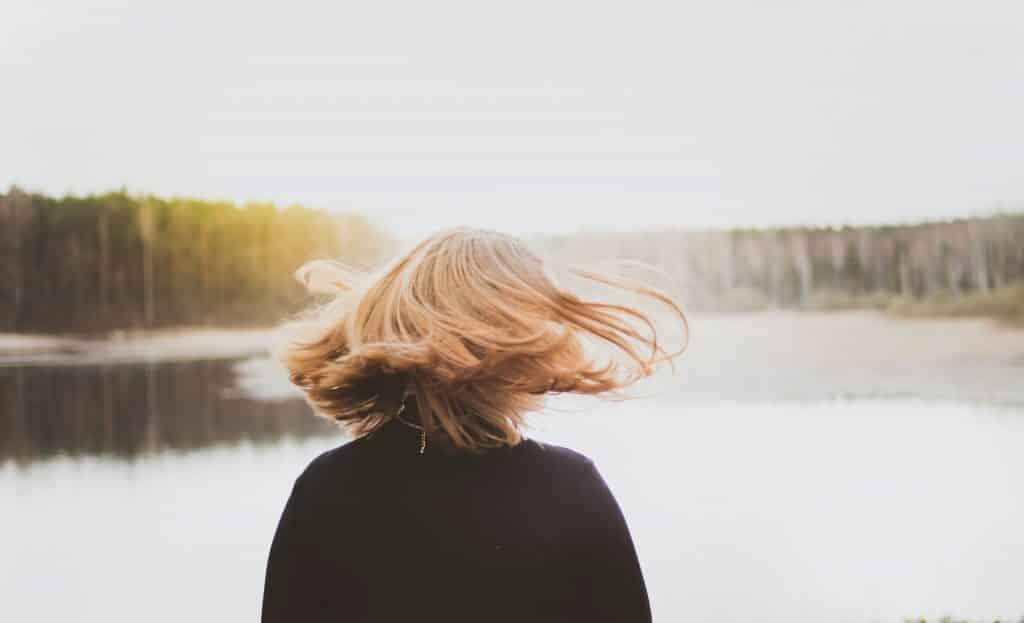 Mulher de costas com os cabelos esvoaçantes, em frente a um rio com árvores em volta.