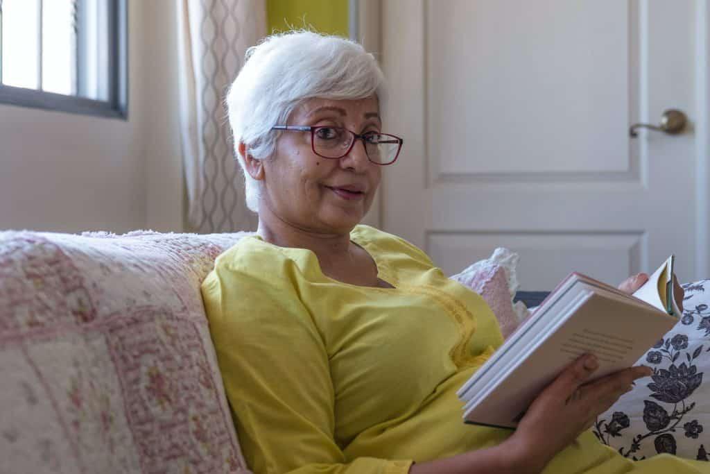 Senhora sentada no sofá segurando um livro aberto
