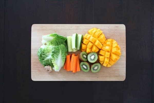 Frutas e legumes em tábua de madeira vistos de cima