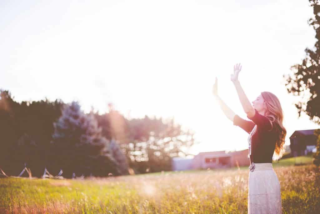 Mulher em campo gramado, com as mãos erguidas para o alto e para frente, em direção a luz do sol.