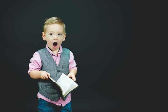 Menino segurando livro com roupa social e expressão de surpresa