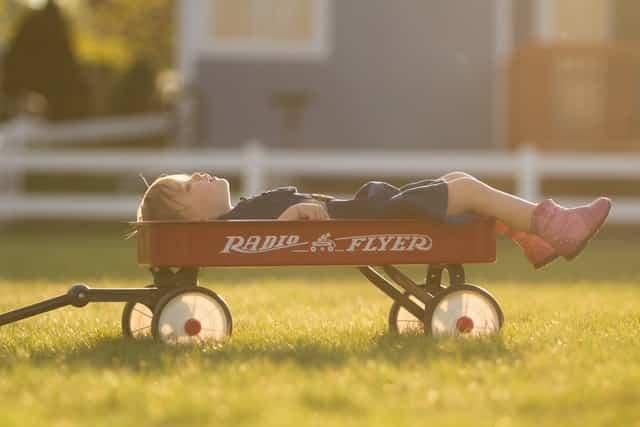 Menina deitada em carrinho de jardim olhando para o alto e gramado