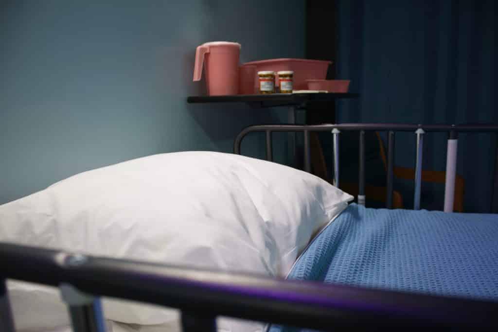 Cama de hospital ao lado de um armário com remédios