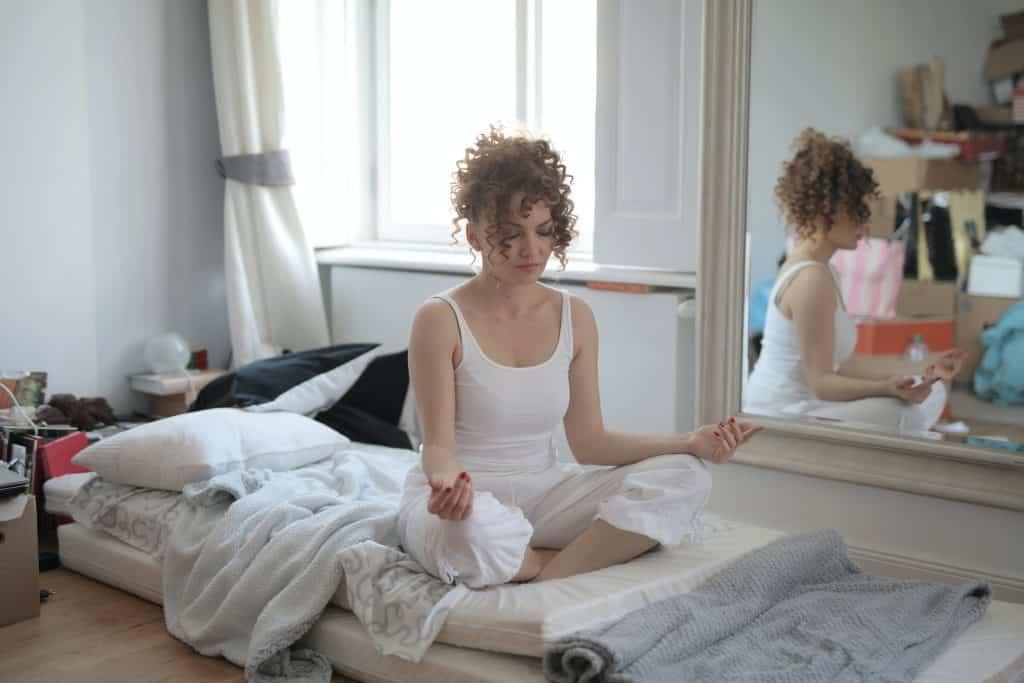 Mulher sentada em um quarto, de pernas cruzadas, meditando.