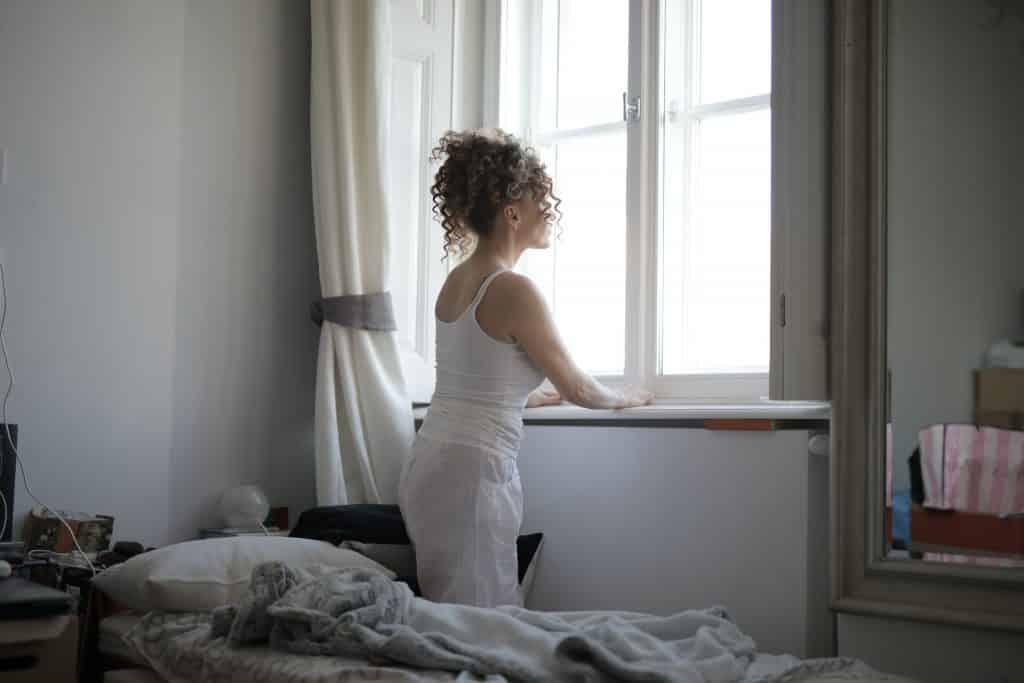 Mulher de cabelos cacheados em um quarto, olhando pela janela.