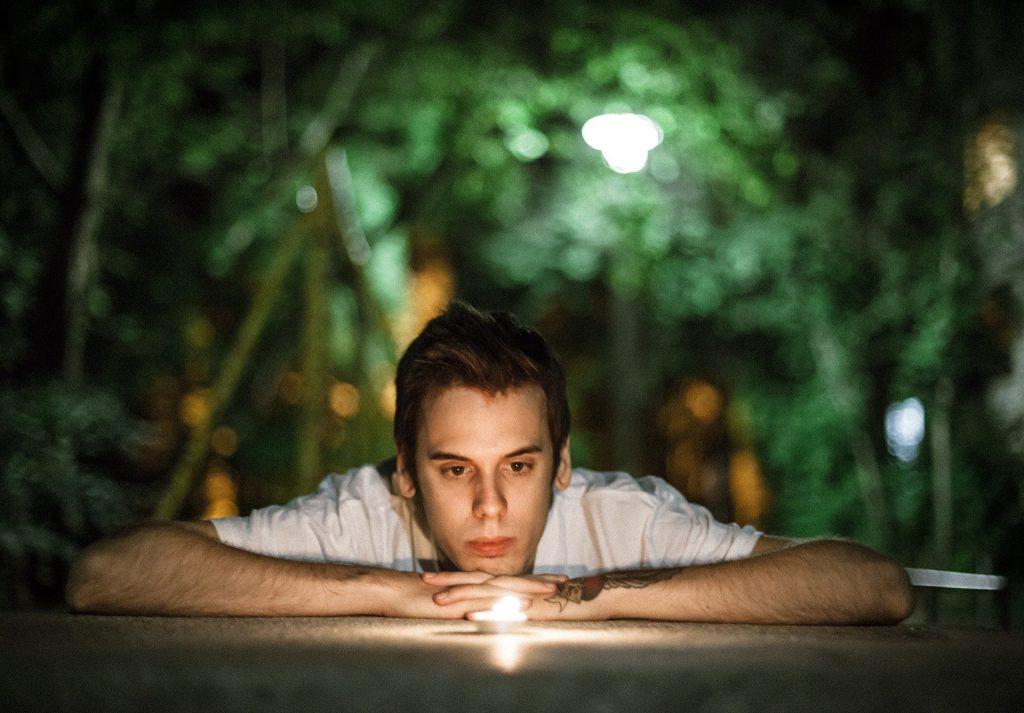 Imagem de um jovem homem debruçado sobre uma mesa olhando para a chama de uma vela.