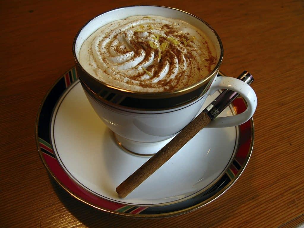 Imagem de uma xícara com capuccino de canela. Ela está sobre um pires e ao lado um pedaço de canela em pau.