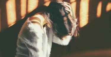 Mulher encostada em uma parede de cabeça baixa segurando com sua mão o canelo caído