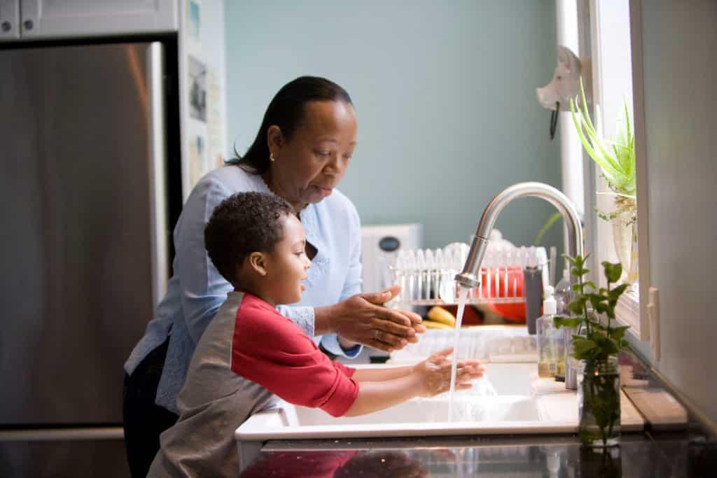 Mãe e filho lavando suas mãos na cozinha