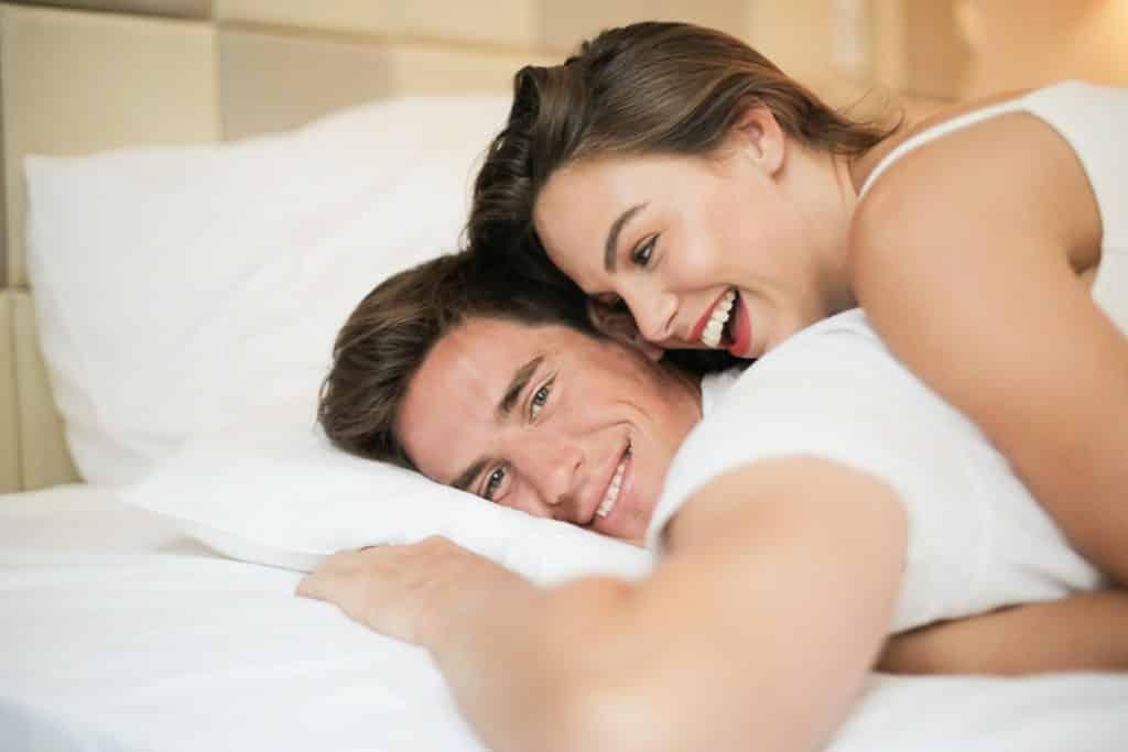 Homem e mulher deitados na cama abraçados, rindo.