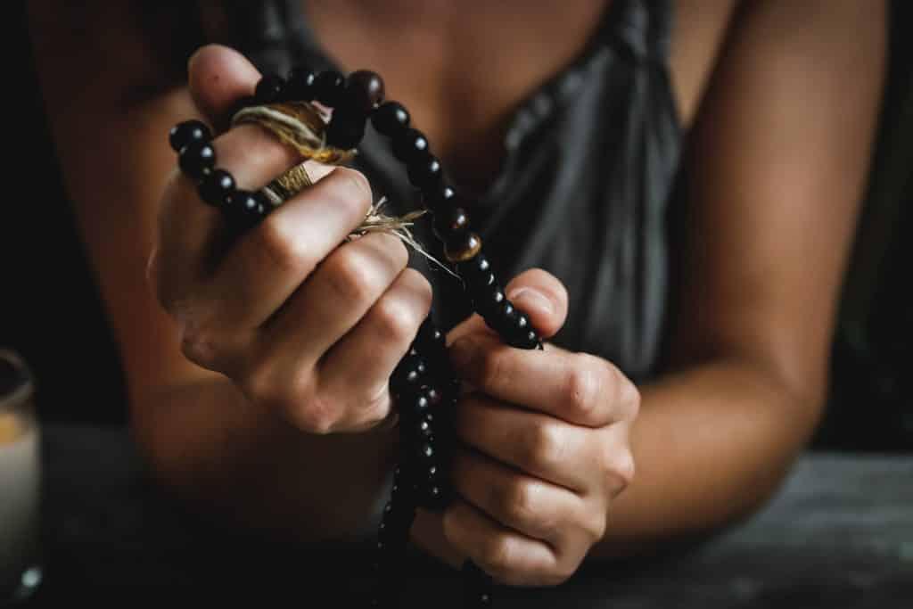 Mulher segurando um terço entre as mãos.