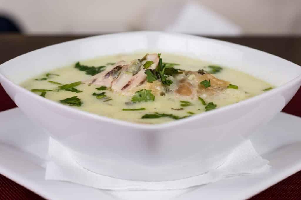 Imagem de uma cumbuca de porcelana cheia de sopa de frango, decorada com salsa e pedaço de frango.
