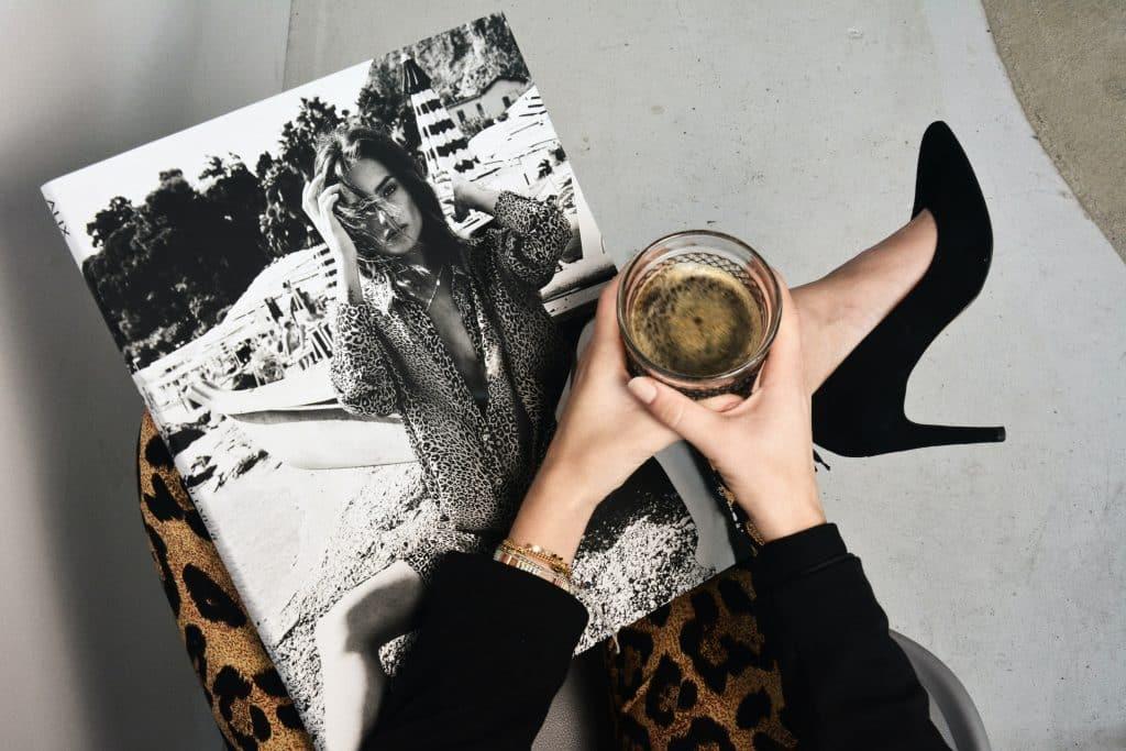 Mulher usando salto segurando uma revista e um copo
