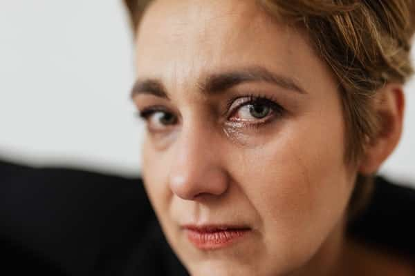 Mulher com olhos molhados e expressão de pânico
