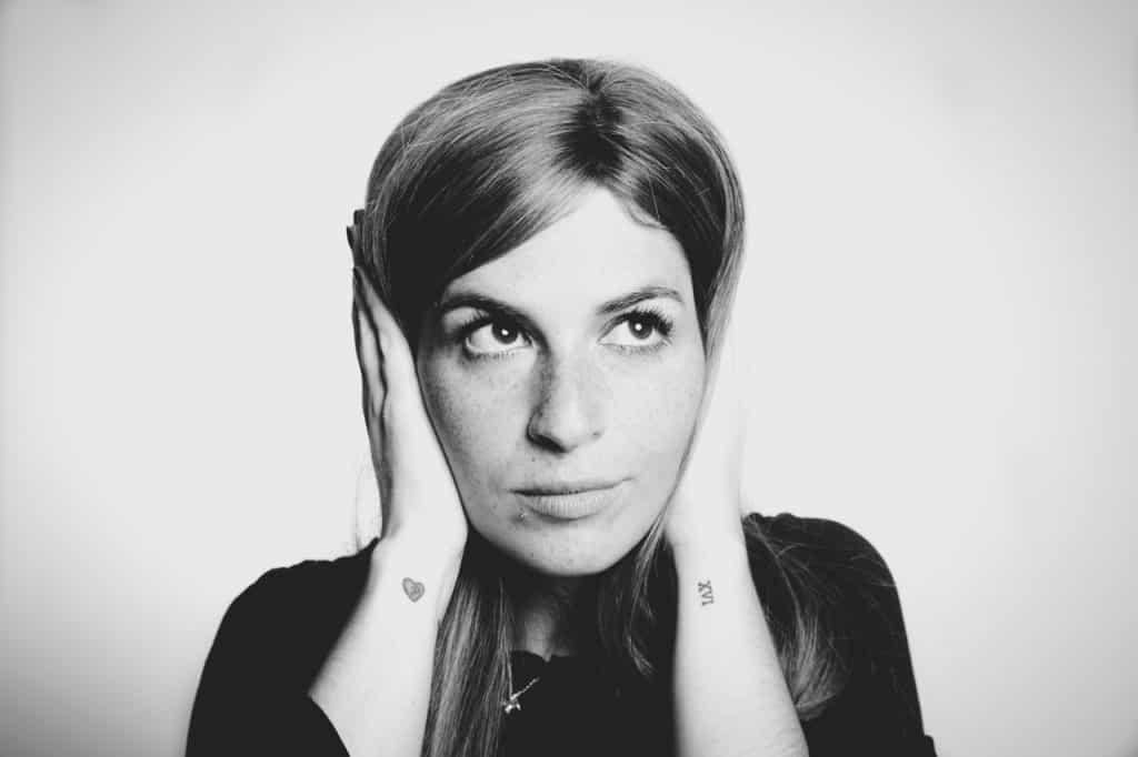 Mulher com expressão fria e as mãos nos ouvidos, para evitar escutar algo.