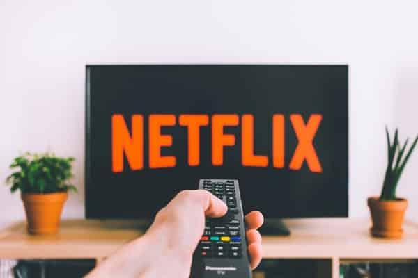Mão segurando controle apontando para TV ligada no início da Netflix