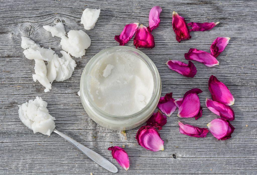 Creme para a hidratação feito à base de óleo de coco. O creme está em um pote de vidro disposto sobre uma mesa de madeira cinza. Ao lado do pote pétalas de rosas rosa.