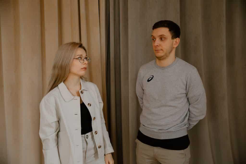 Homem e mulher lado a lado, olhando um para o outro, com expressões sérias.