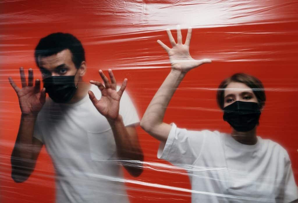 Homem e mulher lado a lado, usando máscaras de proteção, presos por uma parede de plástico.