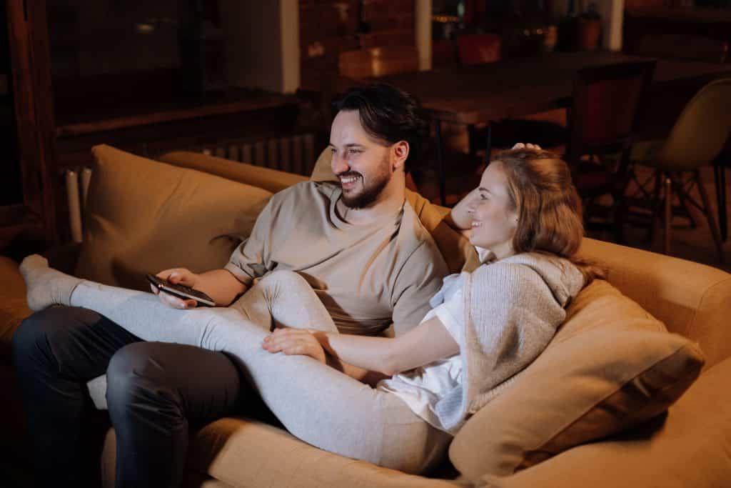 Homem e mulher sentados no sofá, assistindo à televisão enquanto riem.