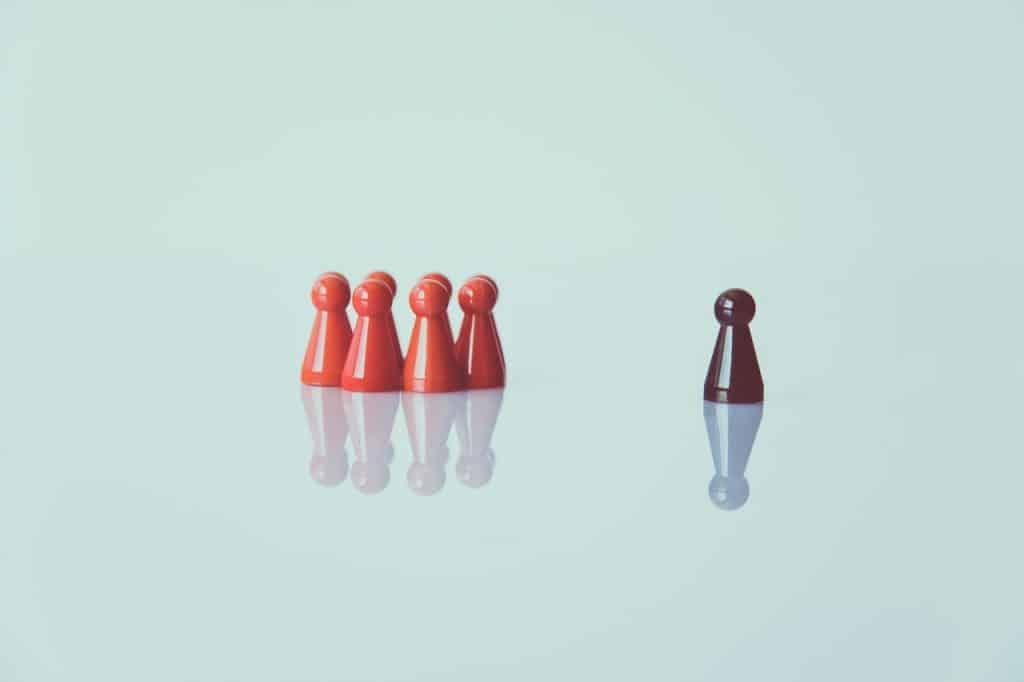 Pequenas peças de jogo de tabuleiro representando pessoas, reunidas em um lado. Do outro lado, uma peça idêntica, mas de cor diferente, está sozinha.
