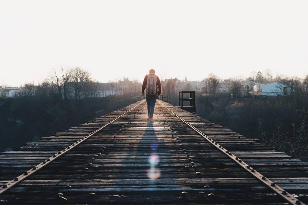 Homem caminhando sobe trilhos em direção ao céu
