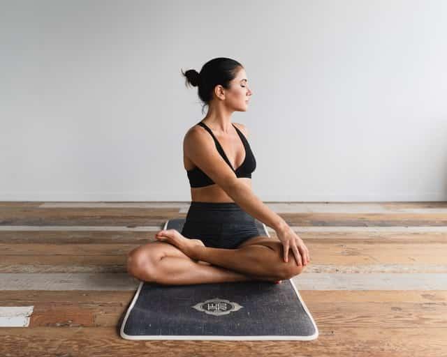 Mulher meditando em tapete em sala