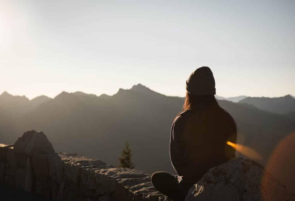 Mulher sentada em uma montanha olhando para o sol