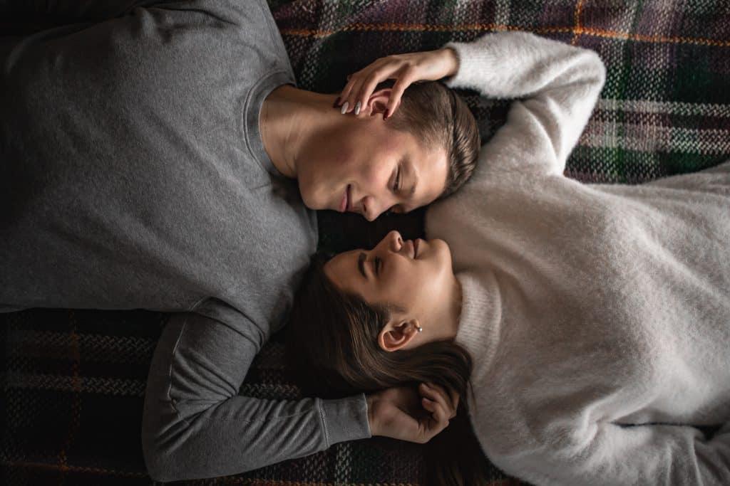 Casal deitado na cama olhando um para o outro com o rosto próximo