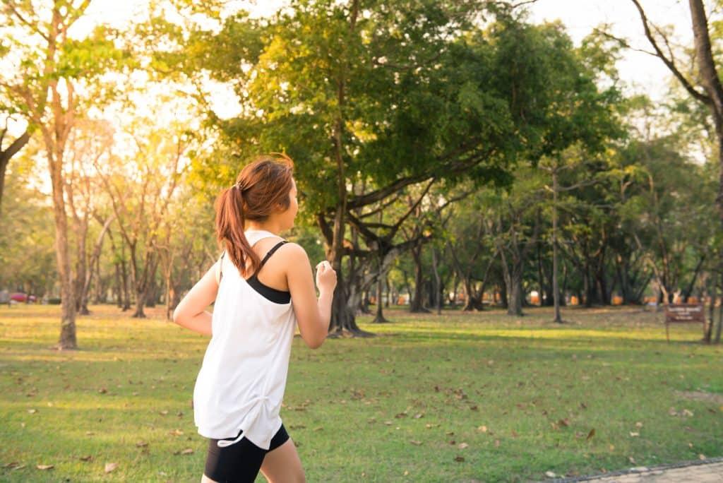 Mulher correndo ao ar livre, em um parque, com roupas de ginástica.