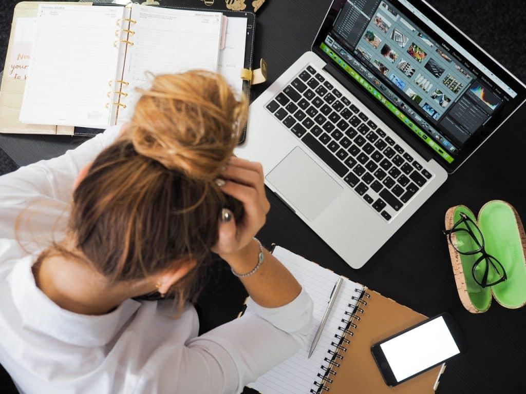 Mulher em frente a computador, com cadernos abertos e o celular ligado ao lado. Ela tem sua cabeça baixa, e as mãos na testa, como se estivesse exausta.