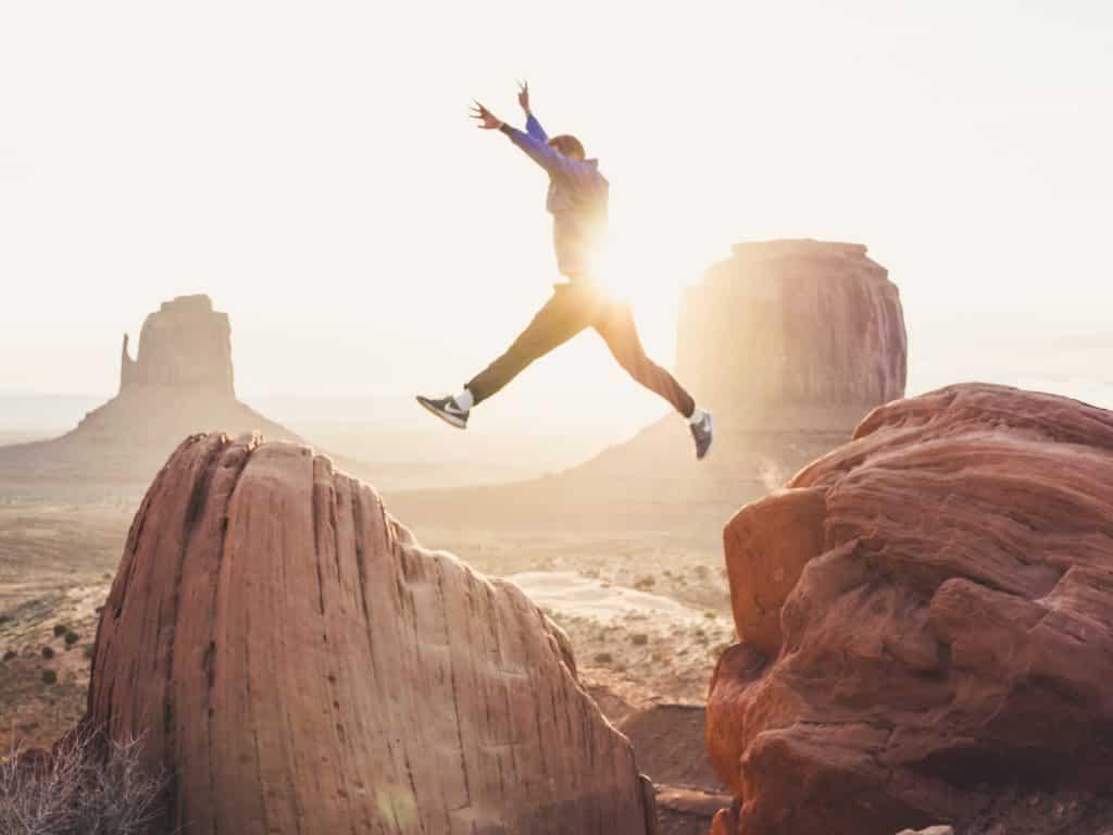 Homem saltando de pedra para outra com sol refletindo ao fundo