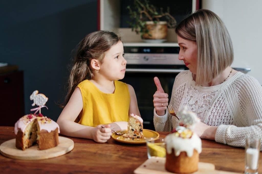 Mulher e menina sentadas lado a lado, em frente a uma mesa com bolos. Elas conversam, e dividem um prato com uma fatia de bolo.