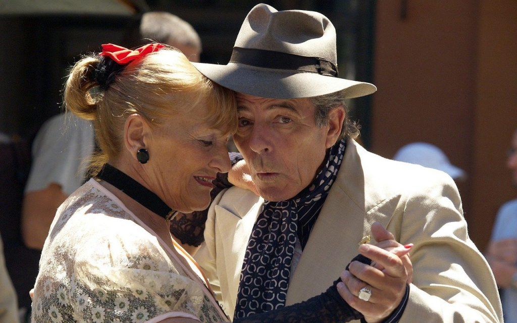 Imagem de um casal (homem e mullher) dançando tango. Eles estão felizes. O homem usa um chapéu cinza e a mulher está com o cabelo preso com um laço vermelho.