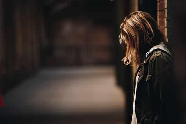 Garota encostada em parede cabisbaixa