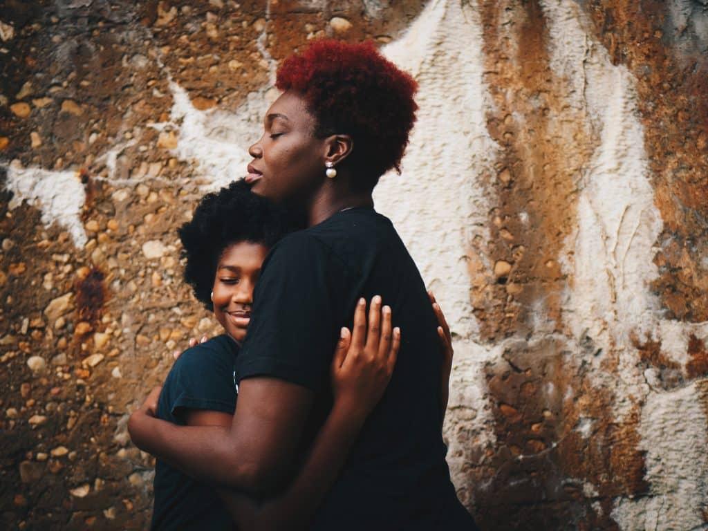 Mãe abraçando a filha.