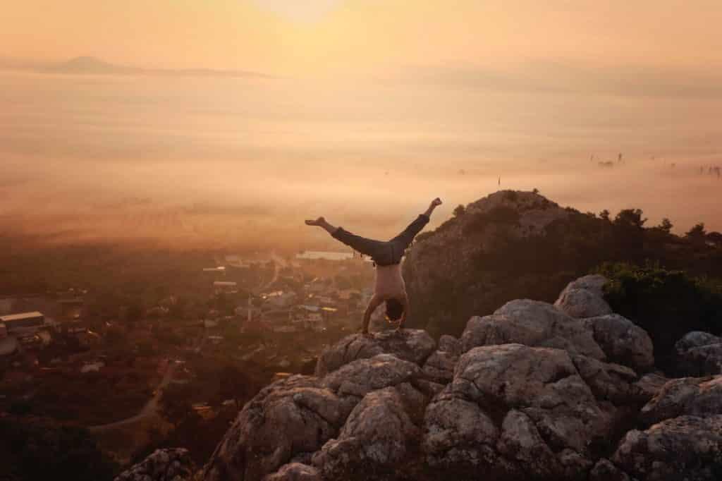 Homem em uma montanha fazendo uma posição de yoga.