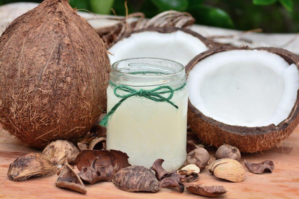 Imagem do óleo de coco em um vidro médio. Ao lado dele um coco inteiro e outro cortado ao meio e algumas castanhas espalhadas.