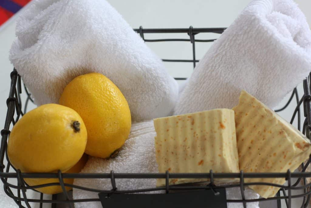 Imagem de uma cesta de arame com pedras de sabão feito de óleo de coco, limões  e três toalhas brancas de banho.