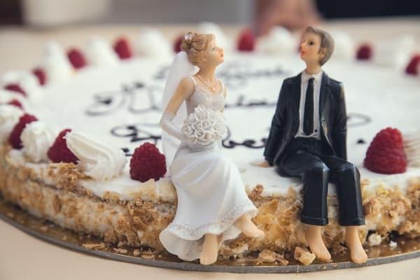 Noivinhos sentados em cima do bolo