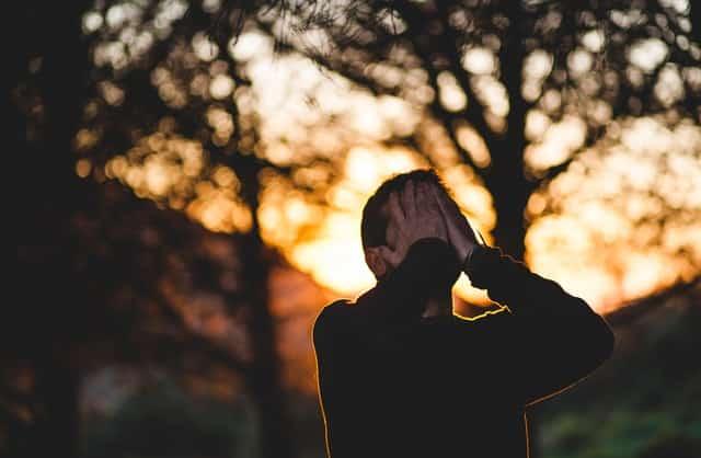 Homem com as mãos no rosto em campo aberto com árvore ao fundo