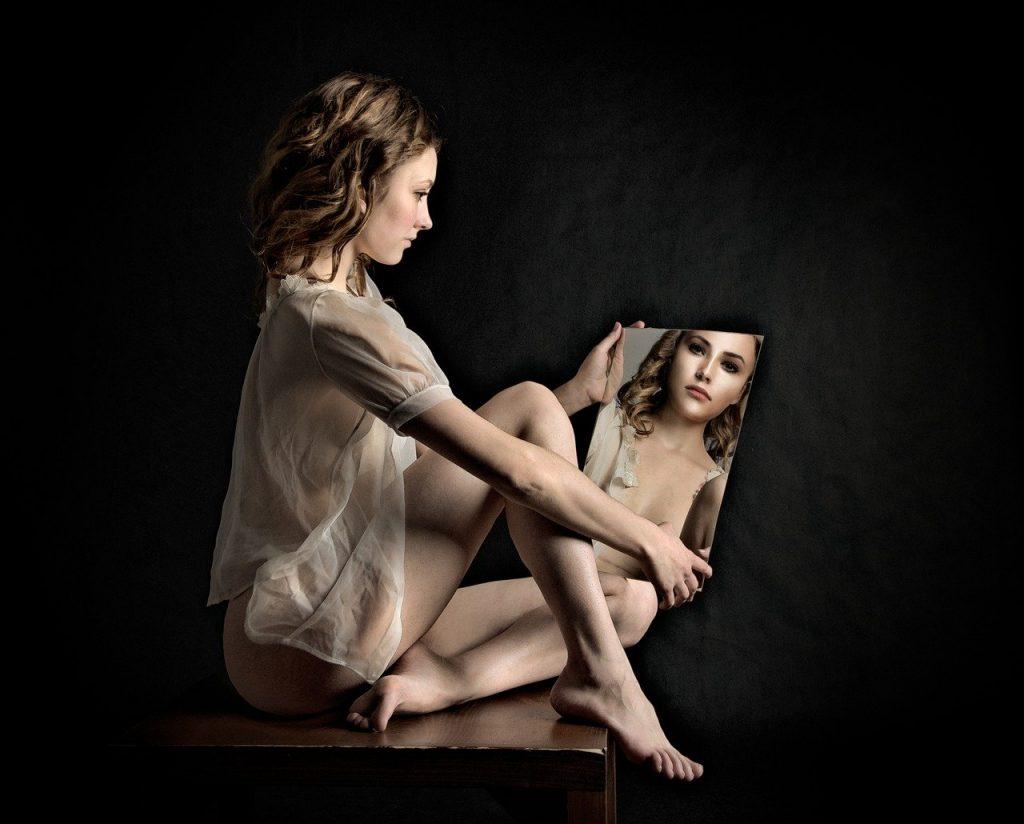 Mulher sentada em cima de uma mesa, com as pernas cruzadas, e segurando um espelho. Ela olha seu reflexo, e a foto mostra ela mesma e seu reflexo.