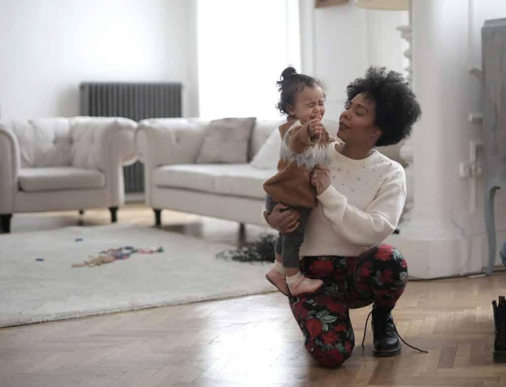 Mulher agachada em chão de sala, segurando menina bebê chorando.