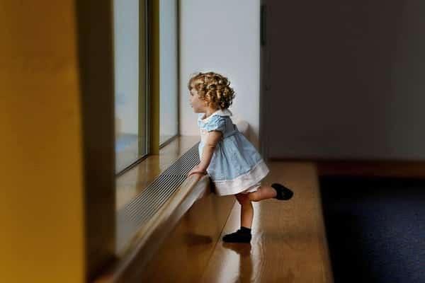 Garotinha de perfil na janela com vestido e pé levantado