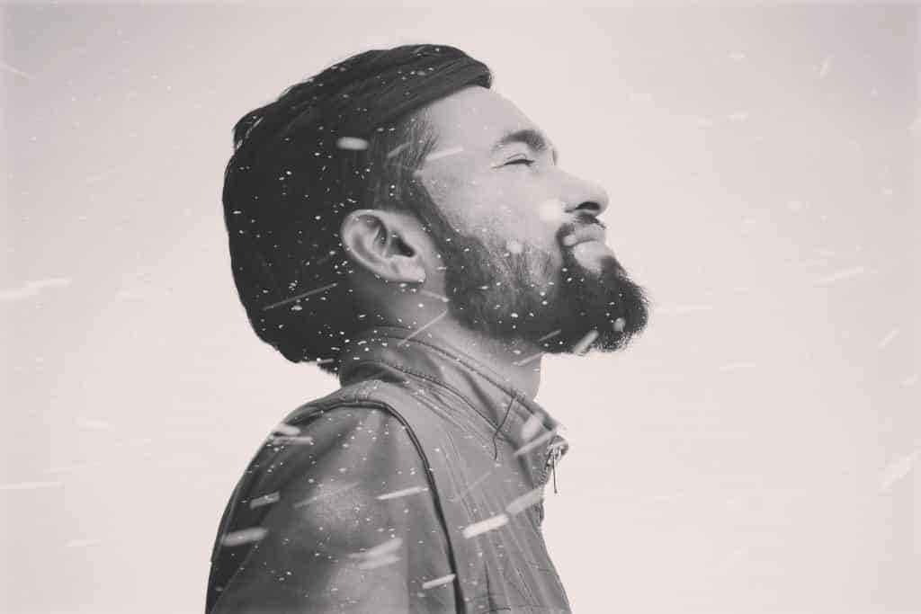 Foto de um homem visto de perfil, com touca e agasalho, de olhos fechados, sorrindo.