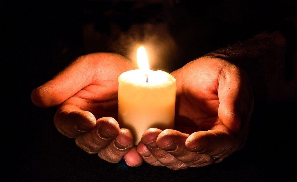 Pessoa segurando uma pequena vela redonda na palma de suas mãos juntas.