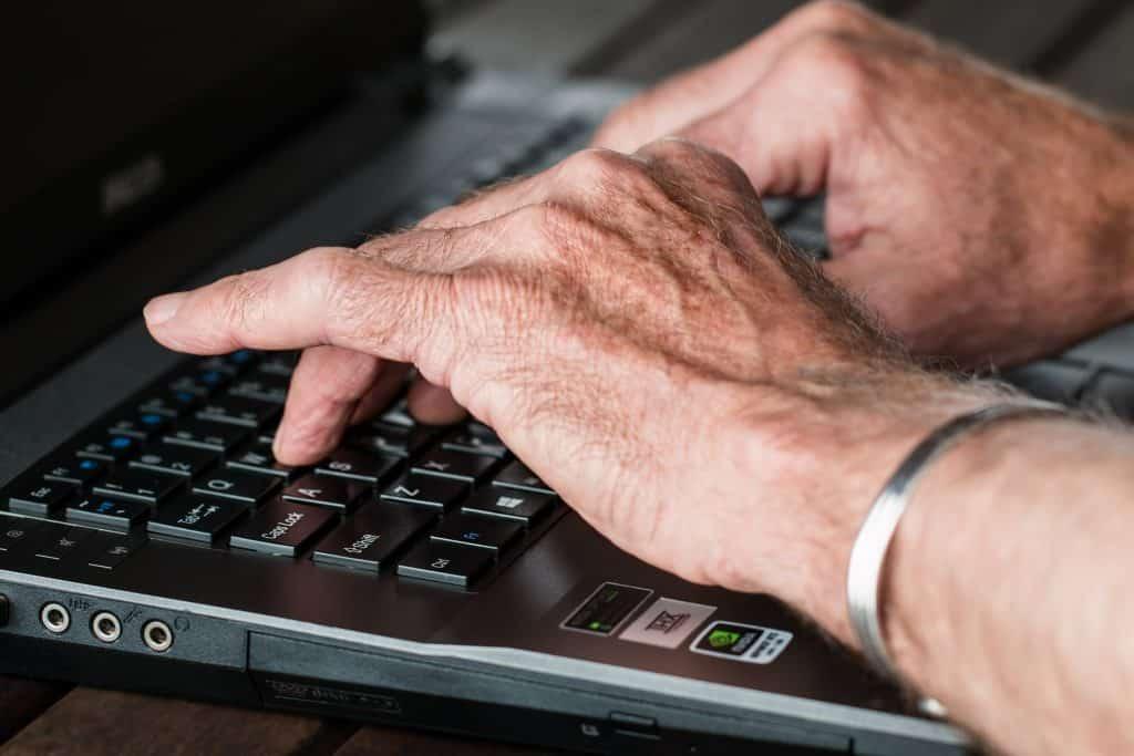 Imagem das mãos de uma pessoa idosa digitando em um notebook.