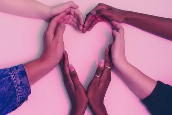 Mãos unidas formando um coração com fundo rosa