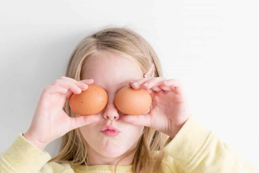 Menina segurando ovos em frente aos seus olhos