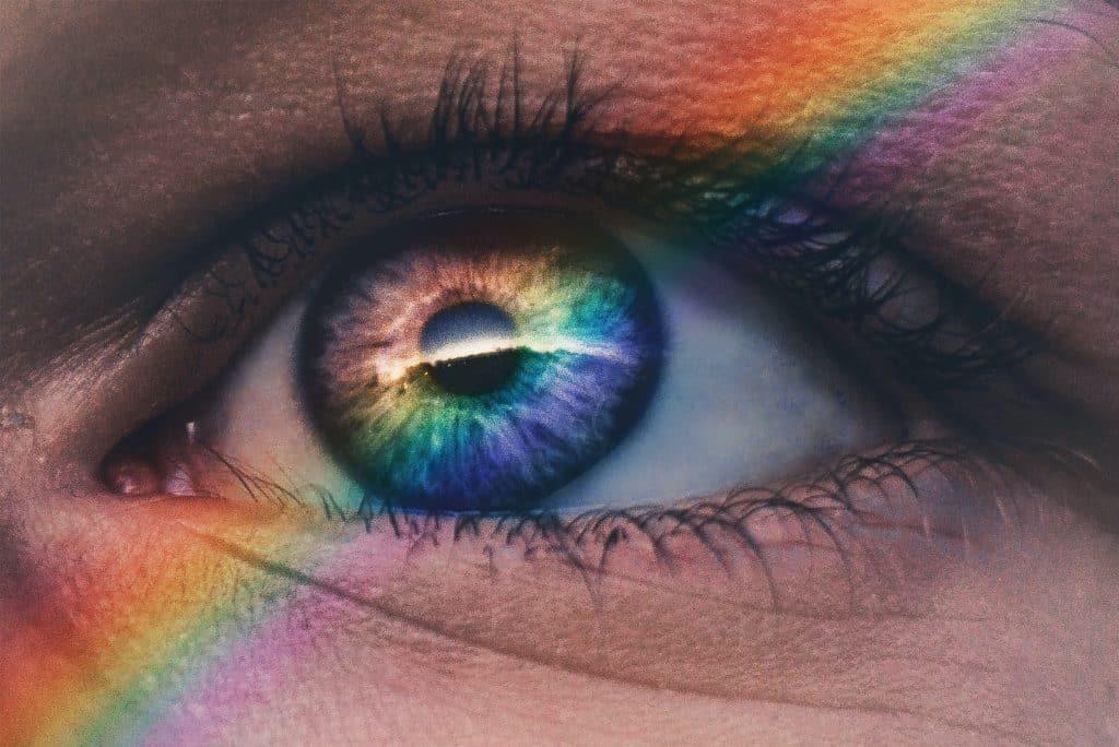 Olho de alguém com reflexo de arco íris